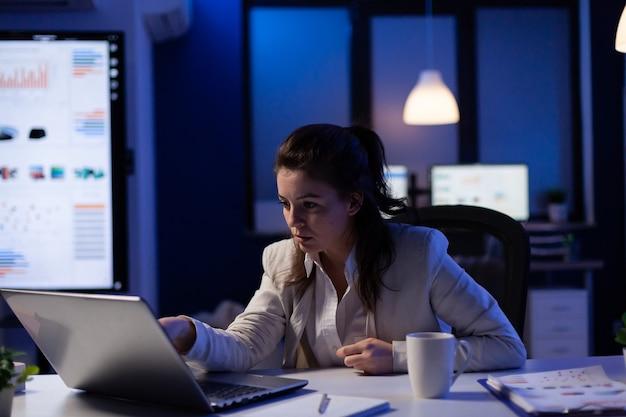 Donna d'affari stressata che controlla i risultati dei profitti in piedi in ufficio a tarda notte