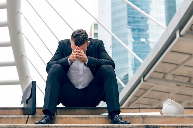 Uomo caucasico sollecitato dell'ingegnere di affari che lavora con il computer portatile sulla scala alla città.