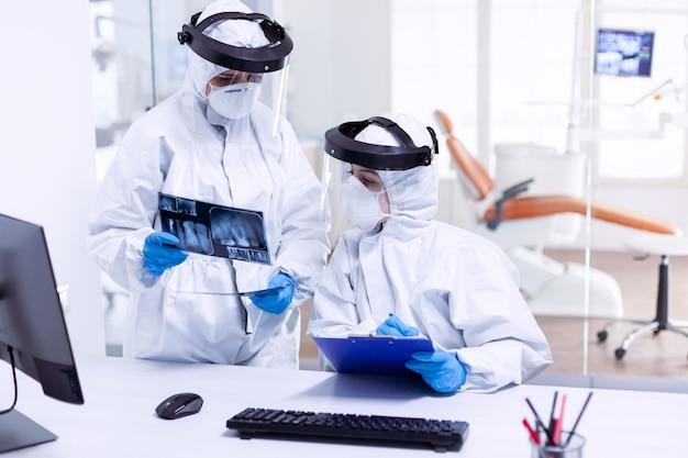 Dentista e infermiere stressati che esaminano i raggi x dei denti indossando una tuta in dpi. specialista medico che indossa indumenti protettivi contro il coronavirus durante l'epidemia globale guardando la radiografia nello studio dentistico.