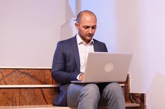 Stressato uomo d'affari esausto che lavora alla scadenza aziendale utilizzando il computer portatile. fiducioso imprenditore aziendale che utilizza laptop facendo gli straordinari seduto sulla tromba delle scale.
