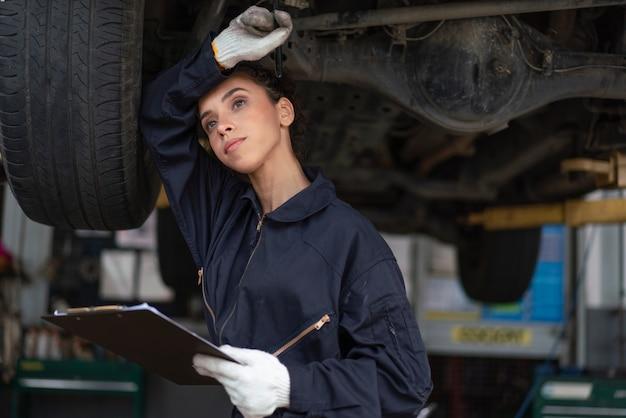 Meccanico femminile stressato che lavora sodo per riparare un'auto nel garage di servizio auto