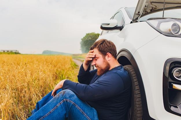 Autista stressato e frustrato che tira i capelli mentre si trovava sulla strada accanto alla macchina rotta. problemi di viaggio e concetti di assistenza. fumo.