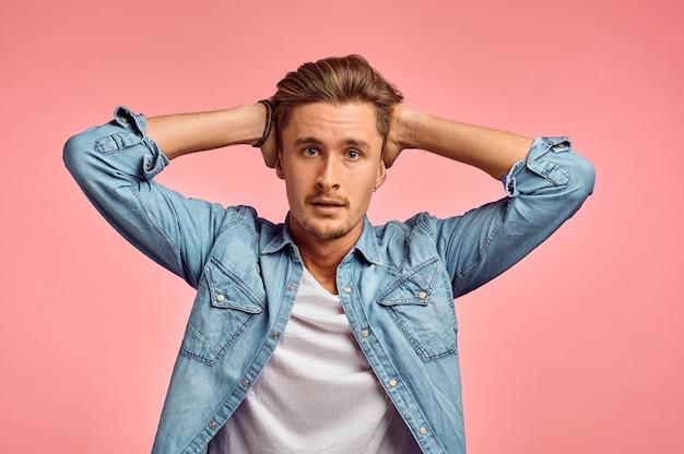 Ritratto di uomo stressato, muro rosa, emozione. espressione del viso, persona di sesso maschile che guarda sulla fotocamera in studio, concetto emotivo, sentimenti