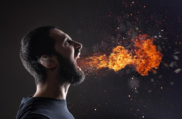 L'uomo stressato urla con il fuoco e il fumo che esce dalla bocca