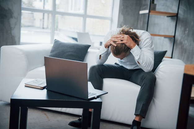 Lo stressato uomo seduto al divano davanti al computer portatile ha abbassato la testa