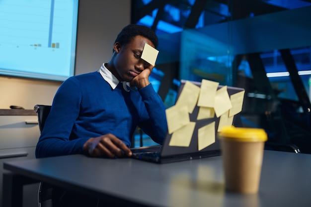 Il manager stressato lavora su laptop, stile di vita notturno in ufficio