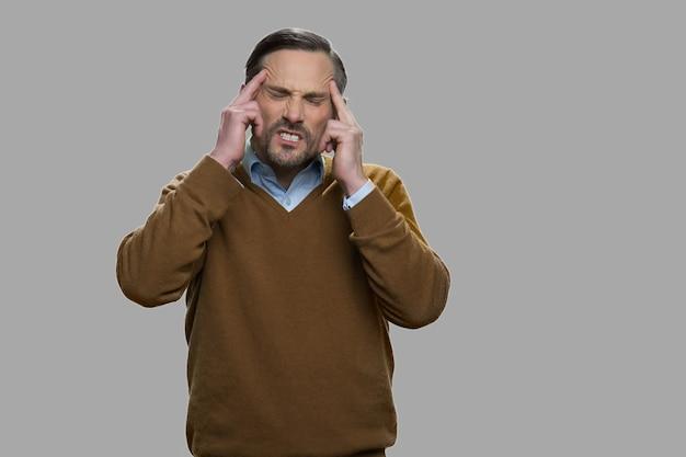 Sottolineato uomo maturo che soffre di mal di testa. uomo malato che ha una terribile emicrania. concetto di problema di salute.