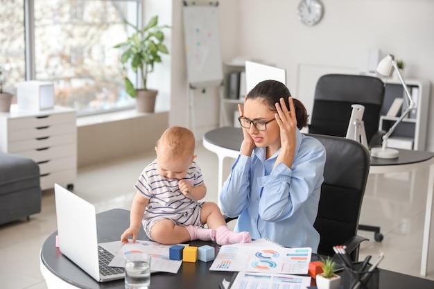 Madre stressata con il suo bambino che lavora in ufficio