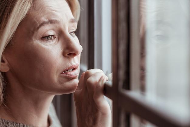 Stressato e triste. donna bionda attraente matura con le rughe del viso che si sente stressata e triste