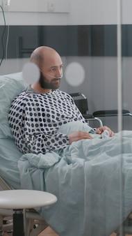 Uomo malato stressato seduto a letto in attesa di cure respiratorie