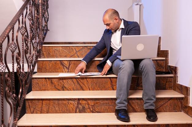 Stressato uomo d'affari stanco di notte sul posto di lavoro che termina la scadenza del progetto. fiducioso imprenditore aziendale che utilizza laptop facendo gli straordinari seduto sulla tromba delle scale.