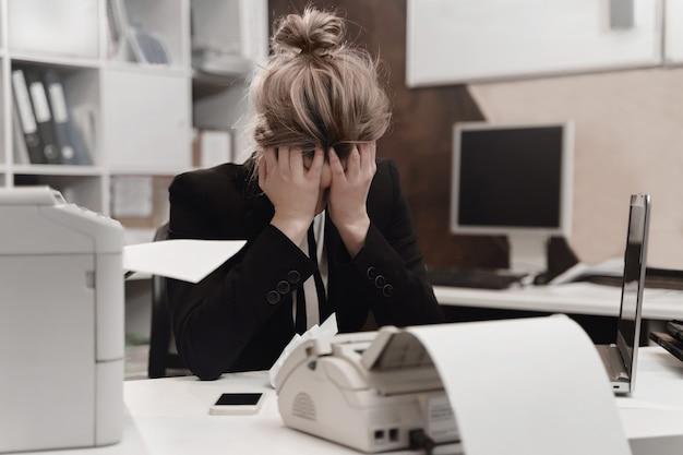 La donna di affari stanca sollecitata si sente esaurita che si siede alla scrivania con il computer portatile