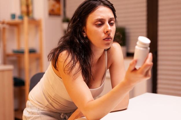 Donna stressata che tiene in mano e guarda la bottiglia di pillole nella cucina di casa pensando ai problemi della vita. preoccupata moglie malata che soffre di emicrania, depressione, malattia e ansia sentendosi esausta con le vertigini