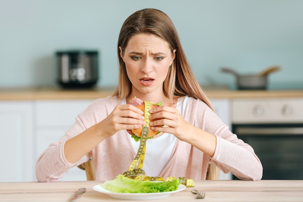 Ha sottolineato la donna che tiene hamburger malsano con nastro di misurazione in cucina. concetto di dieta