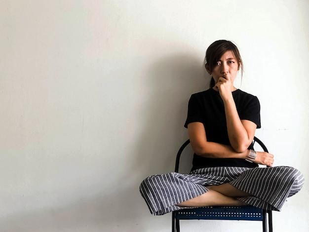 Donna stressata seduta su una sedia, alla ricerca di qualcosa con turbamento e sensazione infelice, sindrome da disturbo depressivo, emozione grave, sul lato destro dello sfondo