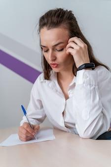 Donna sollecitata che si siede alla tavola. donna oberata di lavoro con documenti.