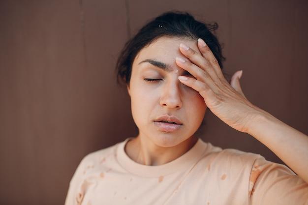 Donna stressata che soffre di colpo di calore rinfrescante con acqua fredda all'esterno. concetto di calore anomalo del tempo.