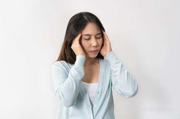 Stressato giovane donna asiatica che soffre di depressione. la signora soffre di emicrania e mal di testa in piedi su sfondo bianco. concetto triste, infelice, deluso. primo piano, copia spazio