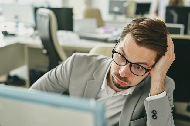 Sottolineato giovane imprenditore in bicchieri che lavorano da soli in ufficio