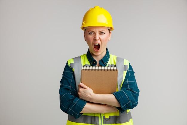 Sottolineato giovane operaio edile femminile che indossa il casco di sicurezza e giubbotto di sicurezza abbracciando il blocco note urlando