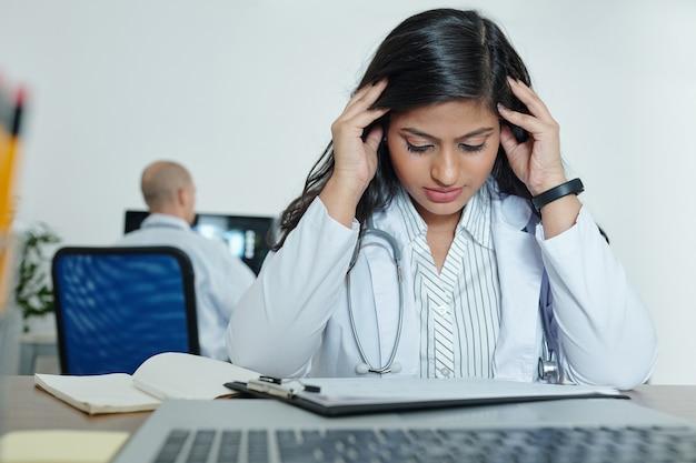 Giovane medico generico stressato che cerca di concentrarsi sul lavoro durante la lettura dell'anamnesi del paziente