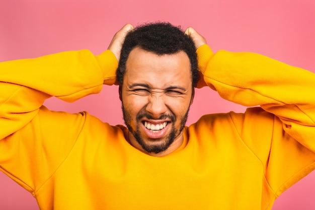 Sottolineato giovane uomo sentire dolore avendo terribile forte mal di testa concetto, stanco sconvolto ragazzo massaggiare templi che soffrono di emicrania isolate su rosa
