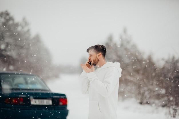 Il giovane sollecitato in felpa con cappuccio bianca parla al telefono con il servizio di emergenza. macchina rotta sulla strada innevata.