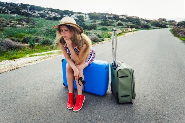 Giovane donna turistica sollecitata che si siede sulle valigie.