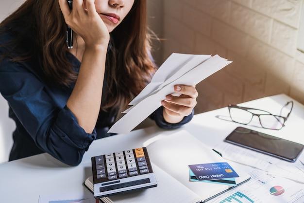 Giovane donna sollecitata che controlla le fatture, le tasse, il saldo del conto bancario e che calcola le spese nel salone a casa