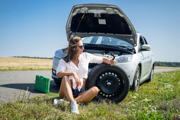 Giovane donna sollecitata che esamina motore della sua automobile. problemi di viaggio su strada. l'auto ha bisogno di una riparazione.