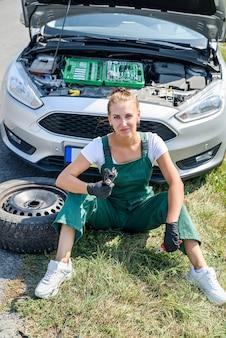 Sottolineato giovane donna guardando il motore della sua auto. problemi di viaggio su strada. l'auto ha bisogno di una riparazione.