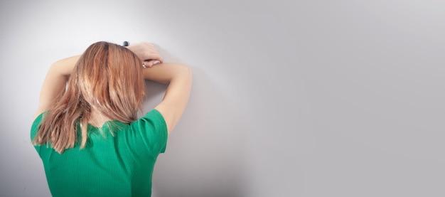 Giovane donna sollecitata vicino alla parete a casa.