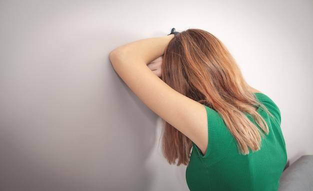 Sottolineato giovane donna vicino al muro bianco a casa