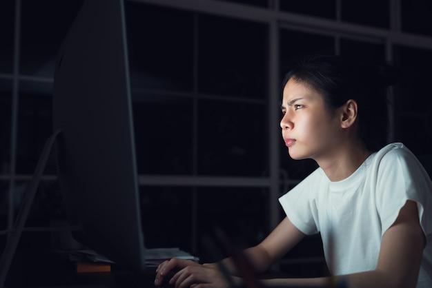 Donna asiatica stressante di affari che si siede sulla sedia e guarda lo schermo del computer in ufficio durante la notte.