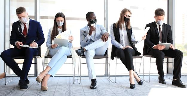 Uomini d'affari stressanti in attesa di un colloquio di lavoro con maschera facciale, quarantena di allontanamento sociale durante l'effetto covid19