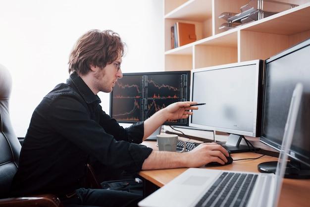 Giornata stressante in ufficio. giovane uomo d'affari che si tiene per mano sul suo fronte mentre sedendosi allo scrittorio in ufficio creativo. concetto commerciale del grafico di finanza dei forex di borsa valori
