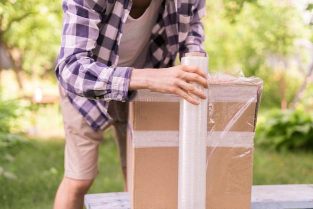 Rotolo di pellicola estensibile, uomo che imballa la scatola per la spedizione