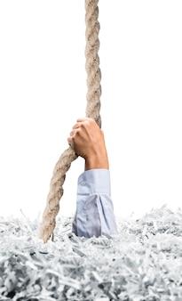 Allunga la mano da un grosso mucchio di fogli bianchi sminuzzati e afferra la corda