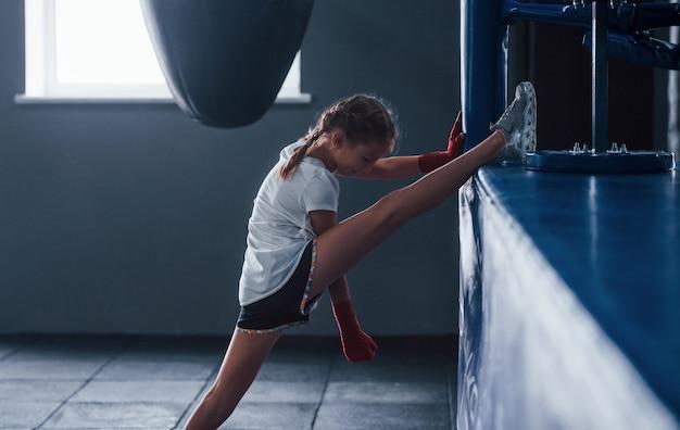 Stretching prima degli esercizi. la giovane bambina in abbigliamento sportivo è in palestra ha una giornata di esercizio. concezione della boxe.