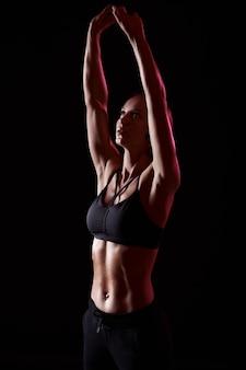 Stretching prima dell'allenamento. ragazza muscolare con braccia forti e addominali ascolta musica in cuffia. uno stile di vita sano