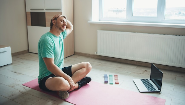 Stretching uomo caucasico è seduto sul pavimento in abbigliamento sportivo e utilizza un laptop durante la sua sessione di fitness