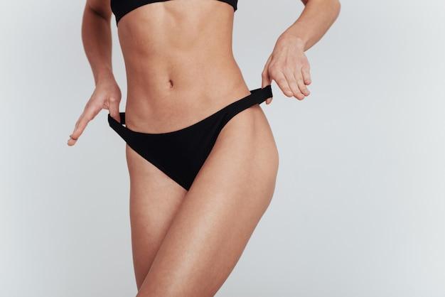 Allungare le mutandine ai lati. la ragazza in biancheria intima con la figura snella mostra il suo corpo al muro bianco.