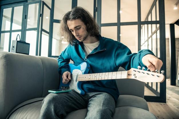 Stringhe di allungamento. bel giovane concentrato seduto sul divano grigio e accordando la chitarra mentre guarda sullo schermo dello smartphone