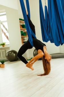 Allenamento di stretching. uno stile di vita sano. la giovane bella ragazza in uniforme nera sta facendo allungando l'esercizio. akroyoga, yoga, fitness, allenamento, sport.