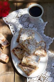 Torta streusel farcita con marmellata di rose, servita con caffè.