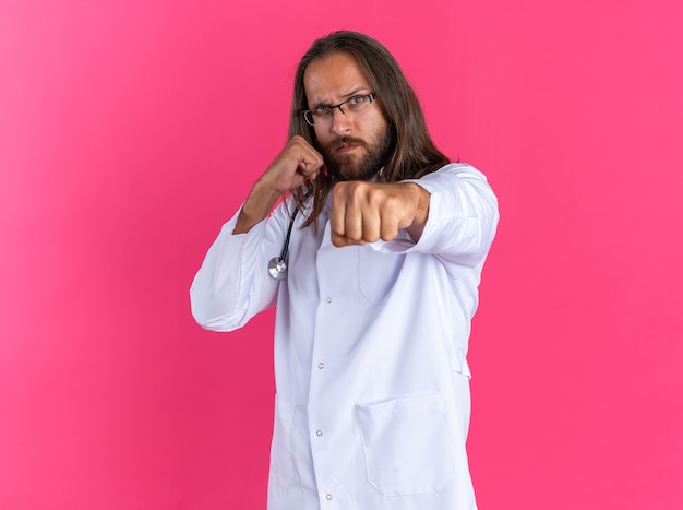Medico maschio adulto rigoroso che indossa accappatoio medico e stetoscopio con occhiali in piedi in vista di profilo guardando la telecamera facendo gesto di boxe isolato sulla parete rosa