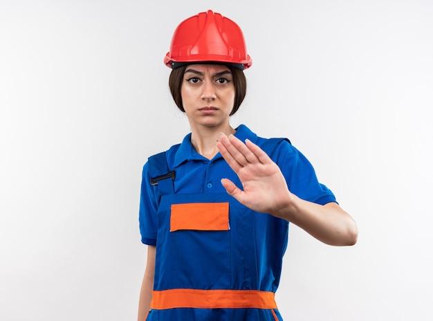 Rigoroso guardando la telecamera giovane donna del costruttore in uniforme che mostra il gesto di arresto