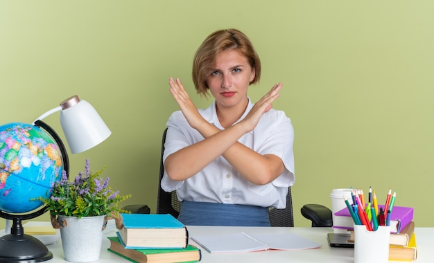 Una giovane studentessa bionda rigorosa seduta alla scrivania con gli strumenti della scuola che non fa alcun gesto