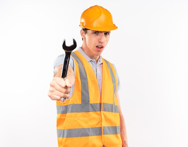 Rigoroso giovane costruttore in uniforme che porge una chiave inglese alla telecamera