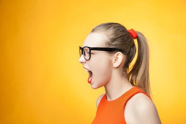 Rigorosa giovane donna con grandi occhiali che urla su uno sfondo arancione brillante